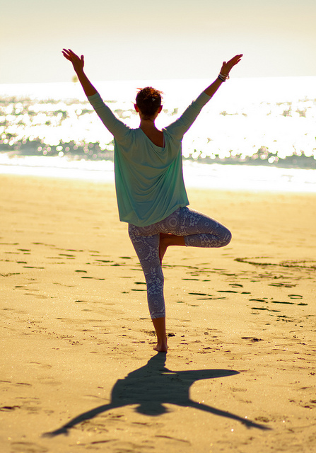 yoga pose on the beach for happiness and wellness